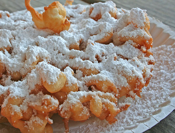 Photo of a funnel cake with powdered sugar on top