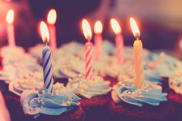 A photo of cupcakes with lit birthday candles